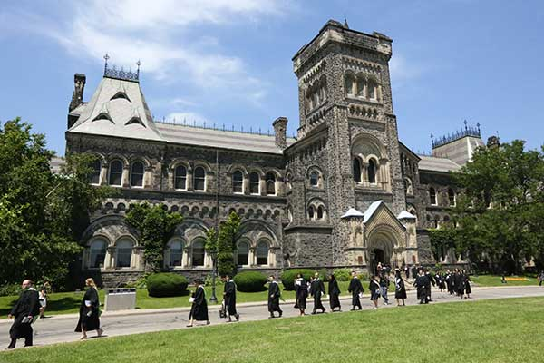 Graduates walking past University of Toronto building, Engineering