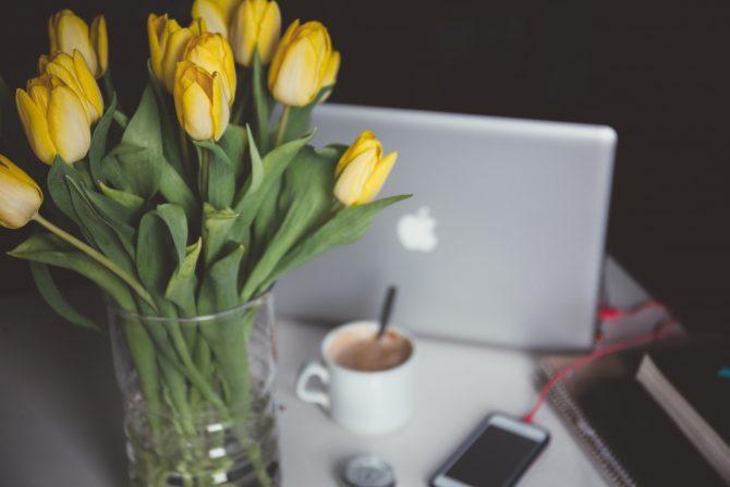 yellow flowers in front of open macbook