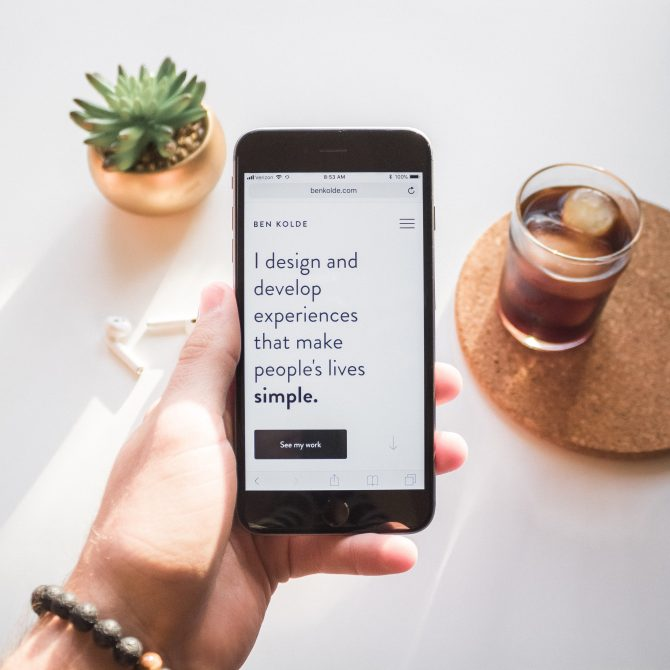 "person holding space iPhone displaying ""i design and develop experiences that make people's lives simple"" text"