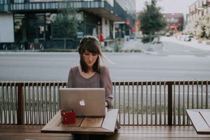 woman sitting outside with open laptop, apply for jobs