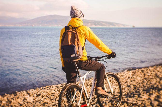 man riding bike near body of water