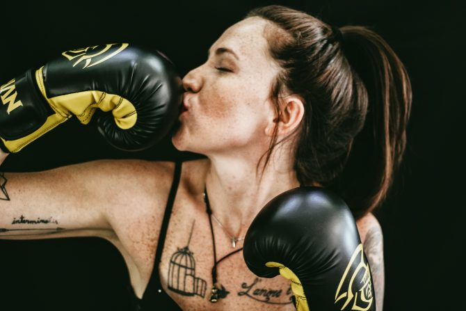 woman kissing black boxing gloves