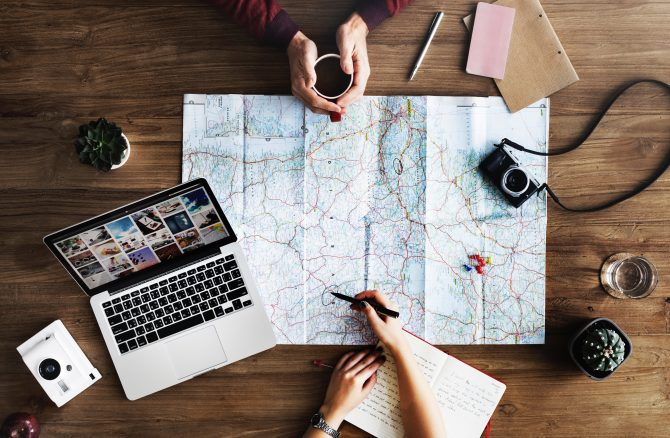 top-view photography of persons holding mug and pen using MacBook and world map, planning for travel