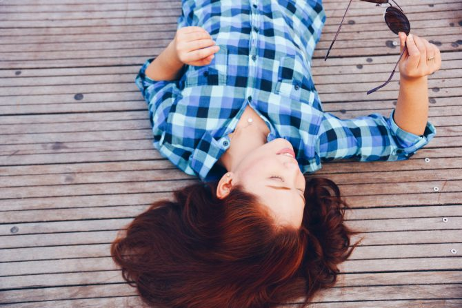 woman lying down with blue flannel shirt