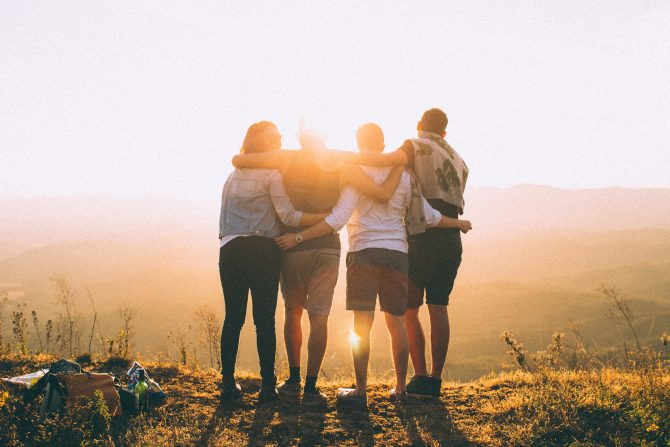 four people standing watching sunset