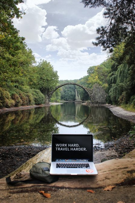 "laptop by river ""work hard, travel harder"""
