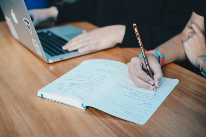two people using macbook, writing