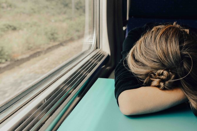 brain fog, tired woman sleeping on train