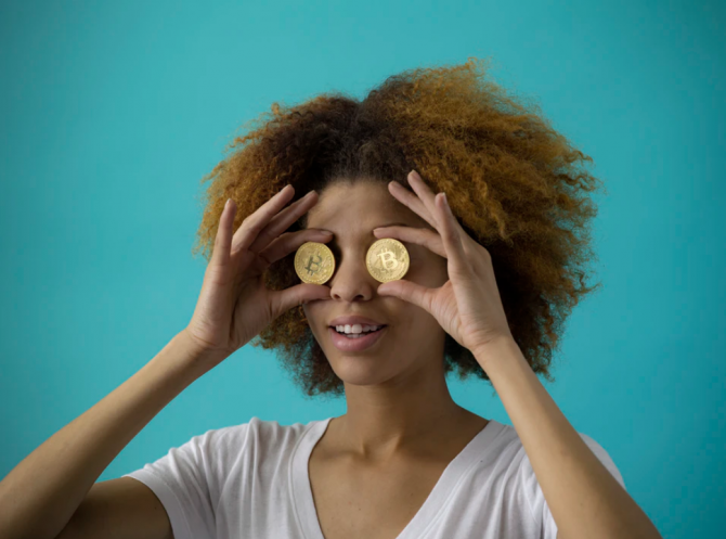 woman holding coins to her eyes