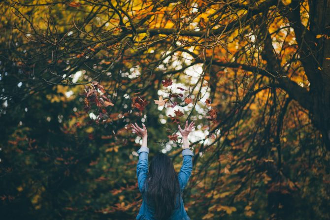 woman standing under changing leaves