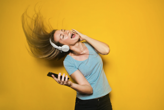 yellow background, woman singing along to music